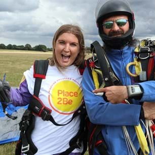 Skydivers, one in Place2Be t-shirt smiling