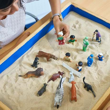 Two people playing with toys in a sandtray
