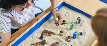 Two people using sand tray with toys in it