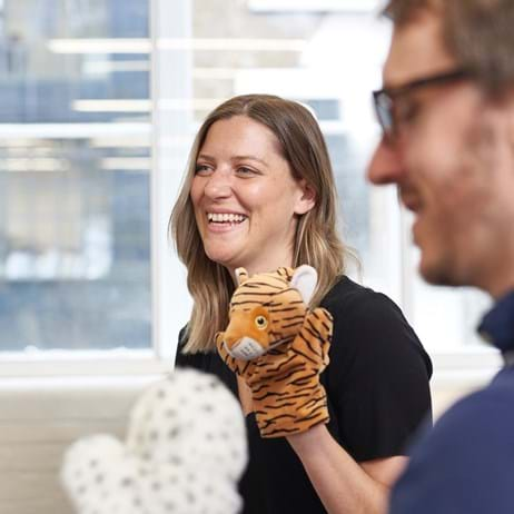 People using puppets to train in counselling & smiling