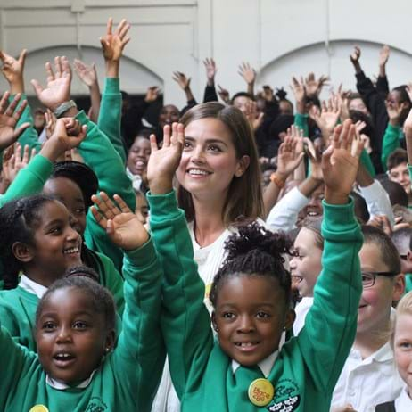 Jenna Coleman with students with arms waving at a Place2Be school