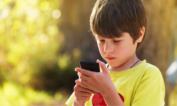 Child outside looking at smart phone