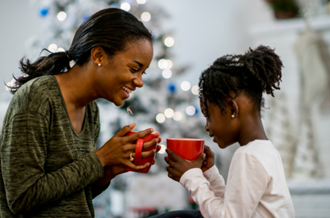 Mother and child holding mugs, sat in front of a Christmas tree