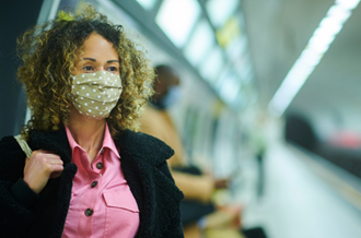 Woman wears facemask on the train platform