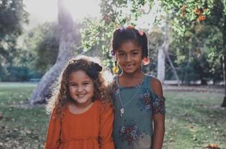 Two young girls standing in a garden smiling at camera