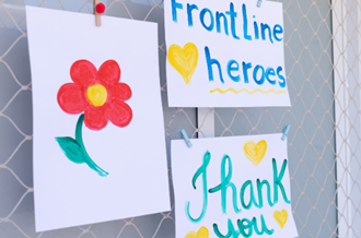 Artwork stuck to a window - a drawing of a flower, a drawing that says 'frontline heroes' and another that says 'thank you'