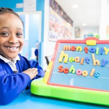 School girl with board spelling out Mentally Healthy Schools