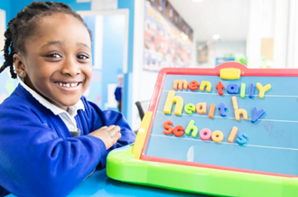 Girl smiling next to magnetic board that says Mentally Healthy Schools