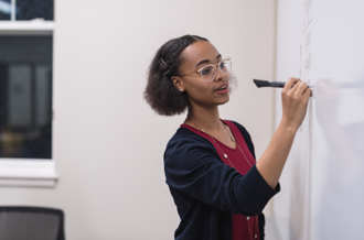 Young woman writes on whiteboard