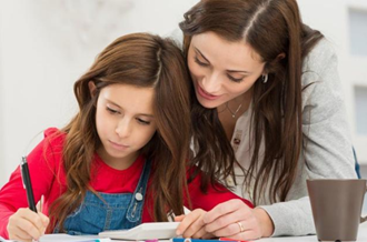 Mother and daughter doing homework on large table