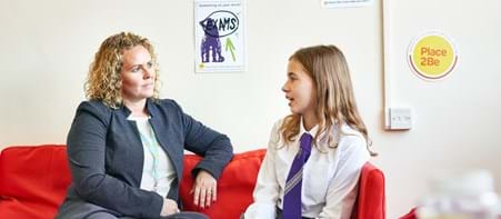 Counsellor sitting on sofa talking to a girl in school