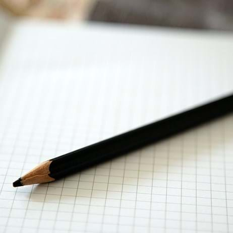 A pencil in a squared notebook, in a classroom