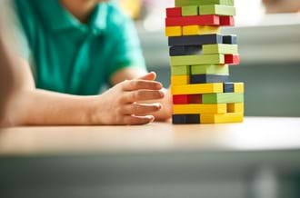 Child with colourful building blocks in school classroom