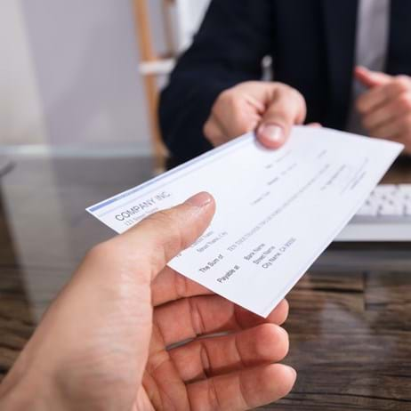 Person handing cheque to another person