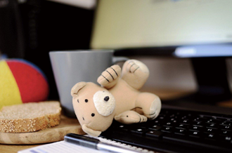 Teddy bear on a computer keyboard, next to a cup of tea and slice of toast