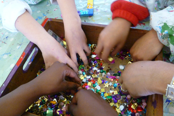 Children's hands picking up craft materials in The Art Room