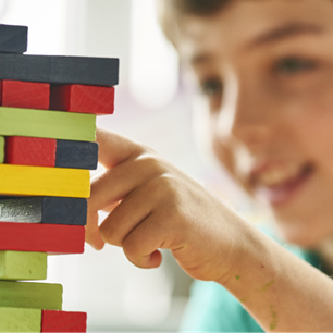 Boy at school playing Jenga with colourful blocks and smiling