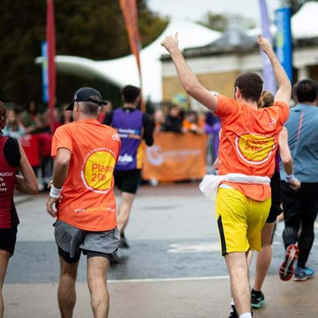 Place2Be runners with one holding hands in the air