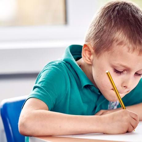 Boy drawing in classroom in school